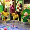 Children in raincoats enjoying the water table exhibit at Imagine It! The Children's Museum of Atlanta.
