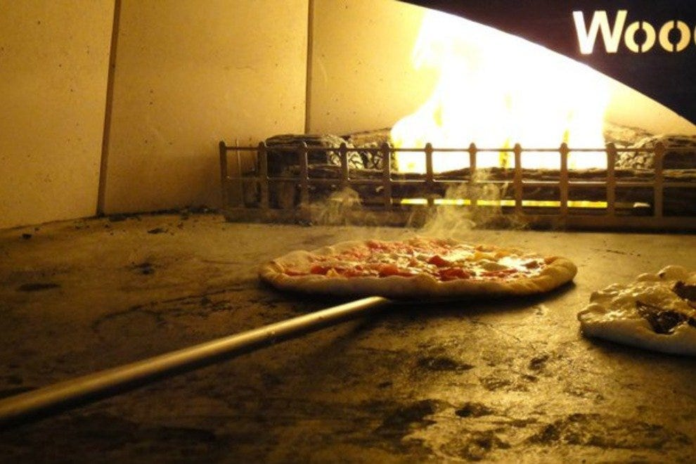 Pizzas going into the wood burning oven