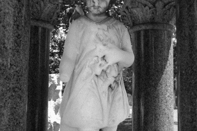 Statue of a child adorning a grave in a Chicago cemetery.