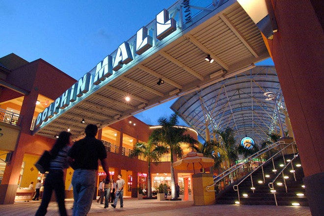 A couple walks beneath the entrance sign to Dolphin Mall.
