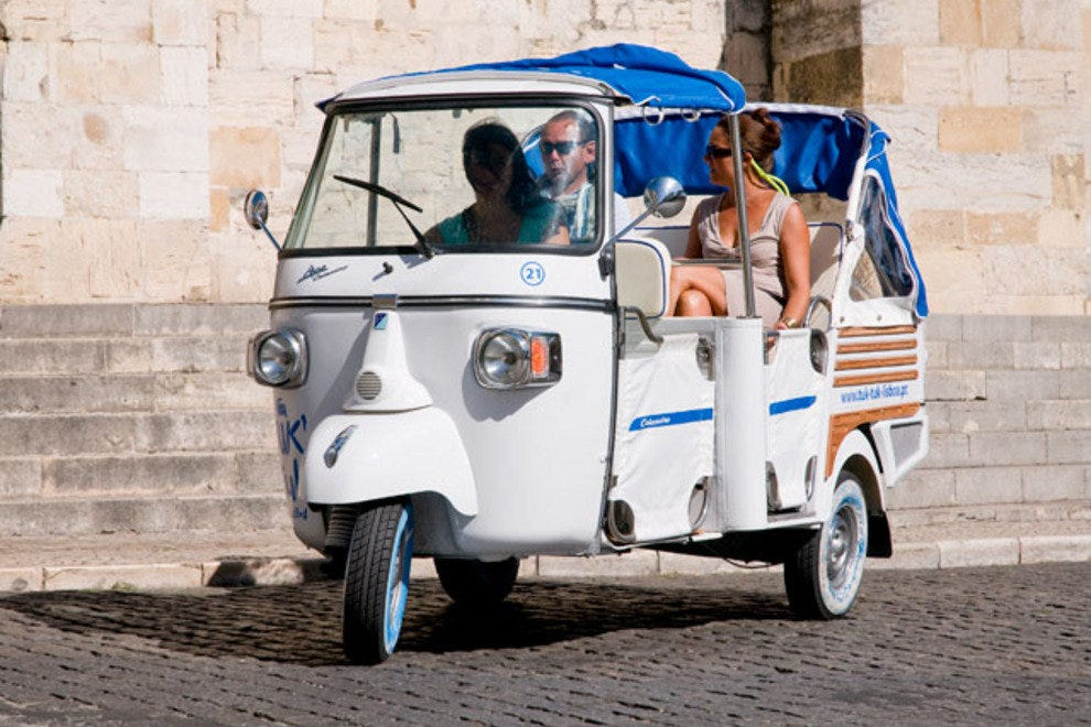 A tuk-tuk with passengers begins its tour from Lisbon's cathedral.