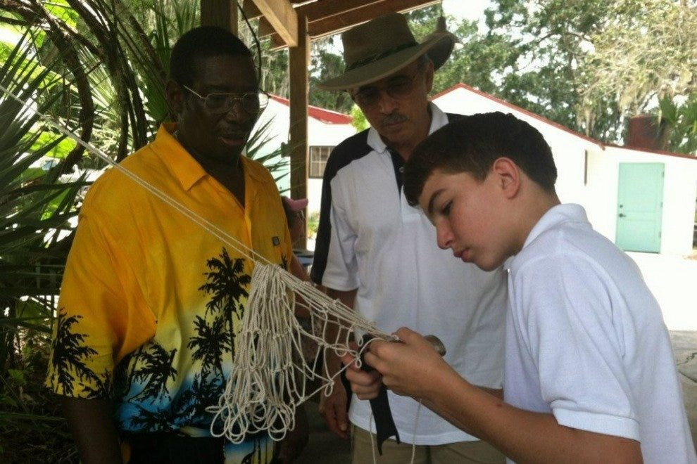 A museum staff member demonstrates the art of net making to guests