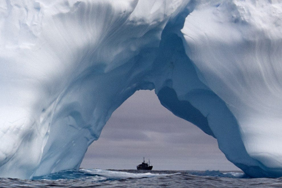 The Steve Irwin seen through an arch of an iceberg.