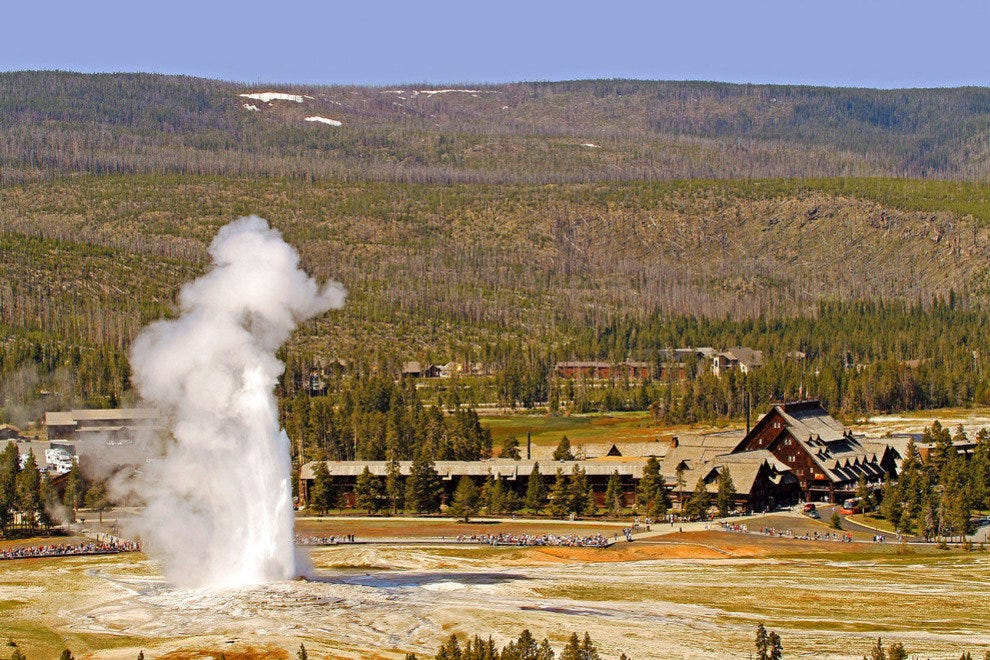 Old Faithful erupts in front of the Old Faithful Inn