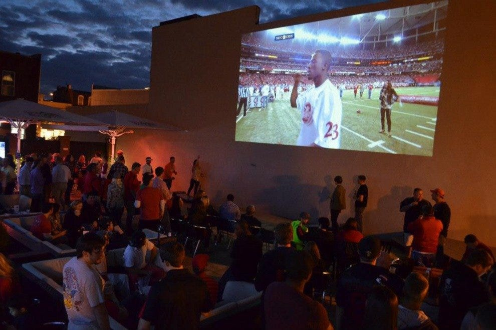 A projector beams games and other televised events onto the wall of the neighboring building