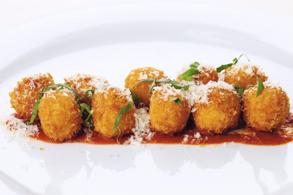 The Tomato-Basil Arancini with fresh mozzarella is just one of the menu items available during Wolfgang Puck's Postrio Bar & Grill's all-day, every day happy hour