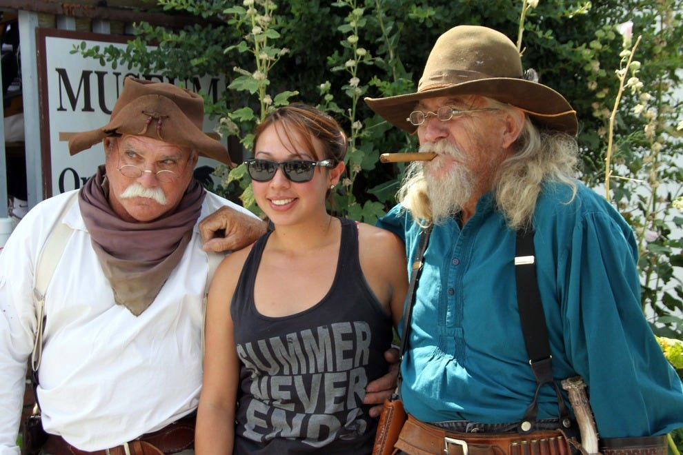 Visitors pose with rugged cowboys in the mountain town of Julian.