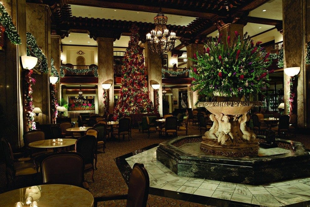 The two-story lobby of the Peabody Hotel is bedecked for Christmas, with a 30-foot tree and lighted garlands