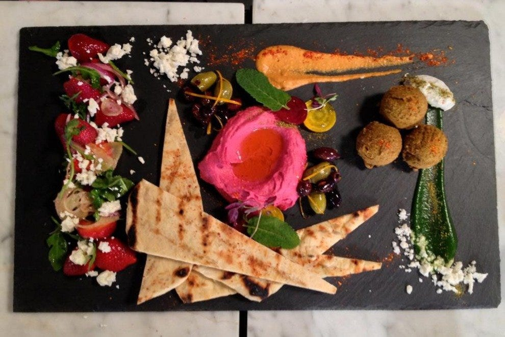Chef Pierola's twist on a mezze platter,with strawberry feta fennel salad,marinated mixed olives,beet hummus,edamame falafel and grilled house flatbread