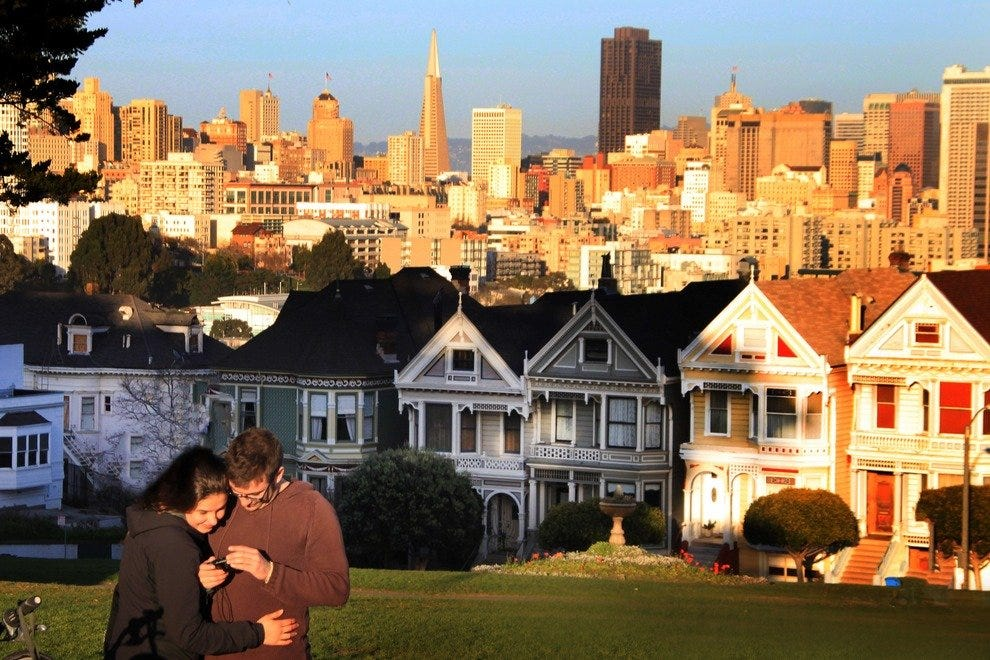 Lovers embrace as sun sets over Alamo Square