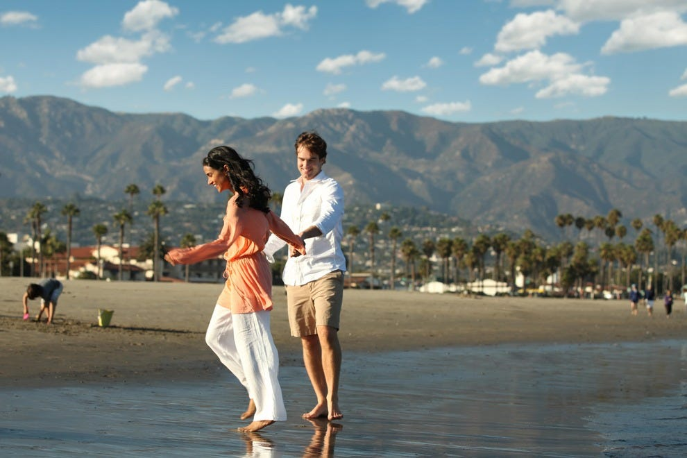 Lovers frolick on the sand on the Santa Barbara beach.