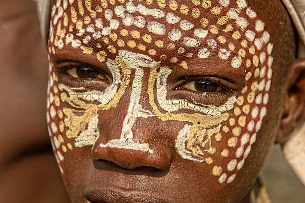A young Arbore boy shows off his paint job