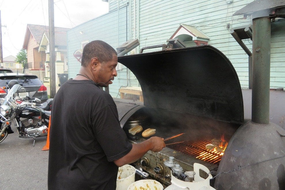 Erik Stewart of BBQ 'n' Some serves charcoal-and-hickory-smoked chicken, ribs, pork and burgers outside of Bullet's