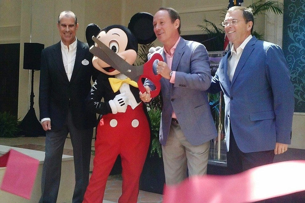 Disney and Four Seasons execs make the opening official with customary giant scissors and the world's most famous mouse