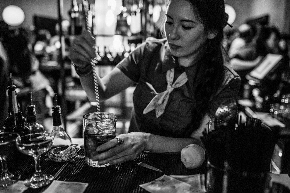 A bartender prepares a drink at Two Ten Jack