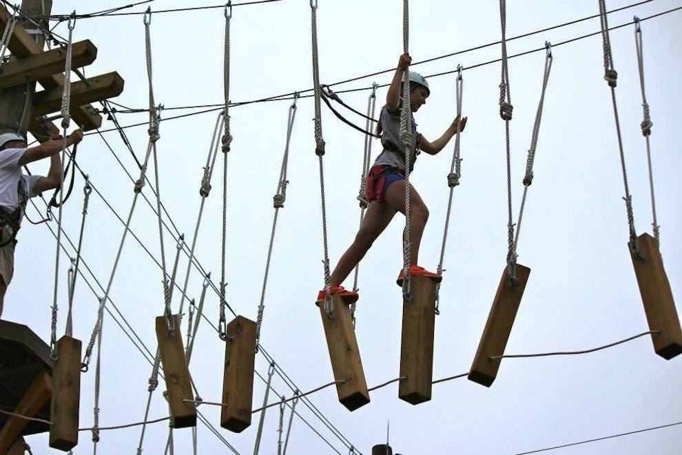 A young adventurer takes on a difficult path through the ropes course.