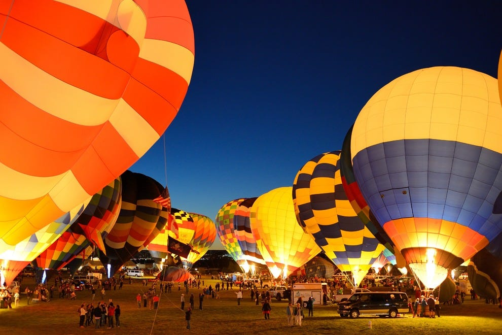 Evening balloon glows involve hundreds of tethered balloons illuminating their envelopes in unison. Spectators stroll through this colorful forest, chatting with pilots from all over the world and warming up when the burners are flared. Popular now throug