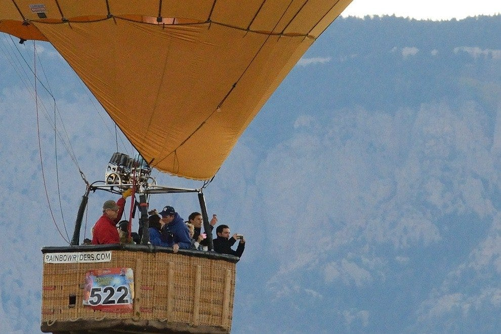A couple steals a kiss during lift off as they drift past the Sandía Mountains. Visitors can experience the Fiesta from the air, click here for more information. For those who prefer to keep their feet on the ground, help is always needed with launching b