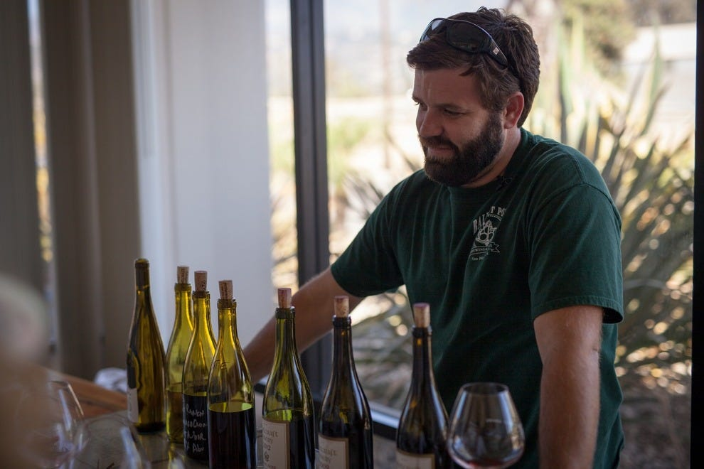 Second-generation winemaker Drake Whitcraft, pouring wines in his tasting room at Whitcraft Winery