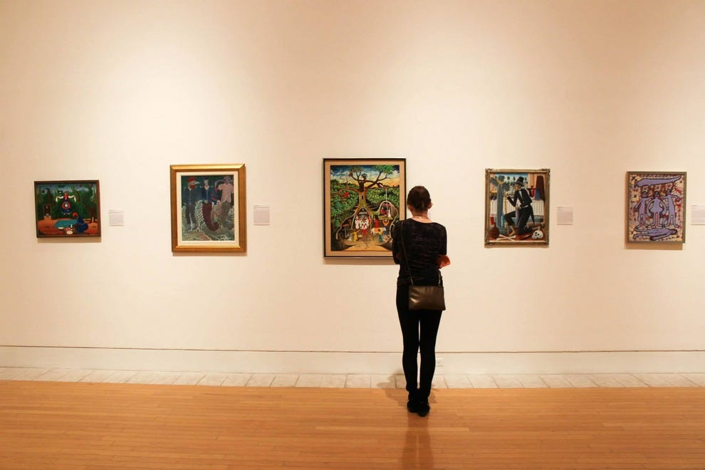 "A museum guest is enthralled by a painting from the ""Transformative Visions"" exhibition"