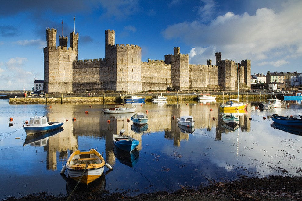 The Welsh countryside is a patchwork of rolling hills and green valleys, with the occasional castle such as Caernarfon perched on a hill.
