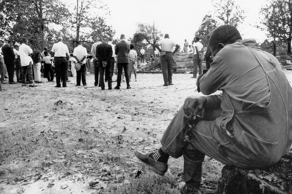 "A mourner grieves at a memorial service for civil rights workers Michael ""Mickey"" Schwerner, James Earl Chaney and Andrew Goodman"