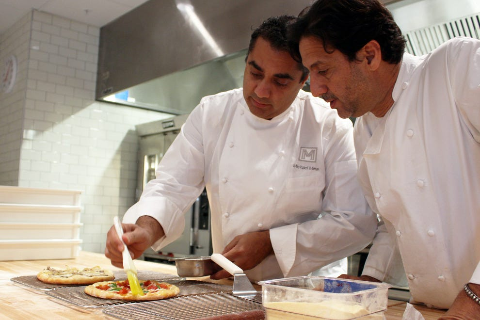 Chefs Michael Mina and Don Pintabona, preparing a meal at FarmTable Kitchen