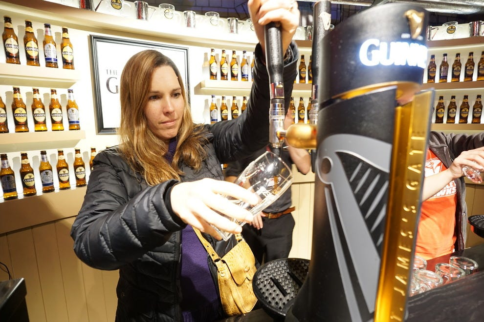 Visitors learn how to perfectly pour a pint of Guinness at the Guinness Academy