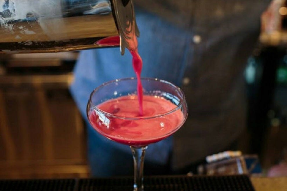 A Mason Social bartender pours a Taylor Made drink featuring hibiscus-infused gin with lemon