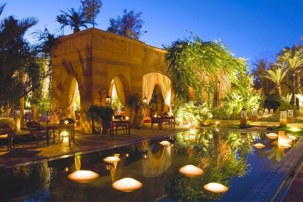Dar Rhizlane, a small hotel in Marrakech, is a study in exotic allure with its softly lit pool and lush gardens.