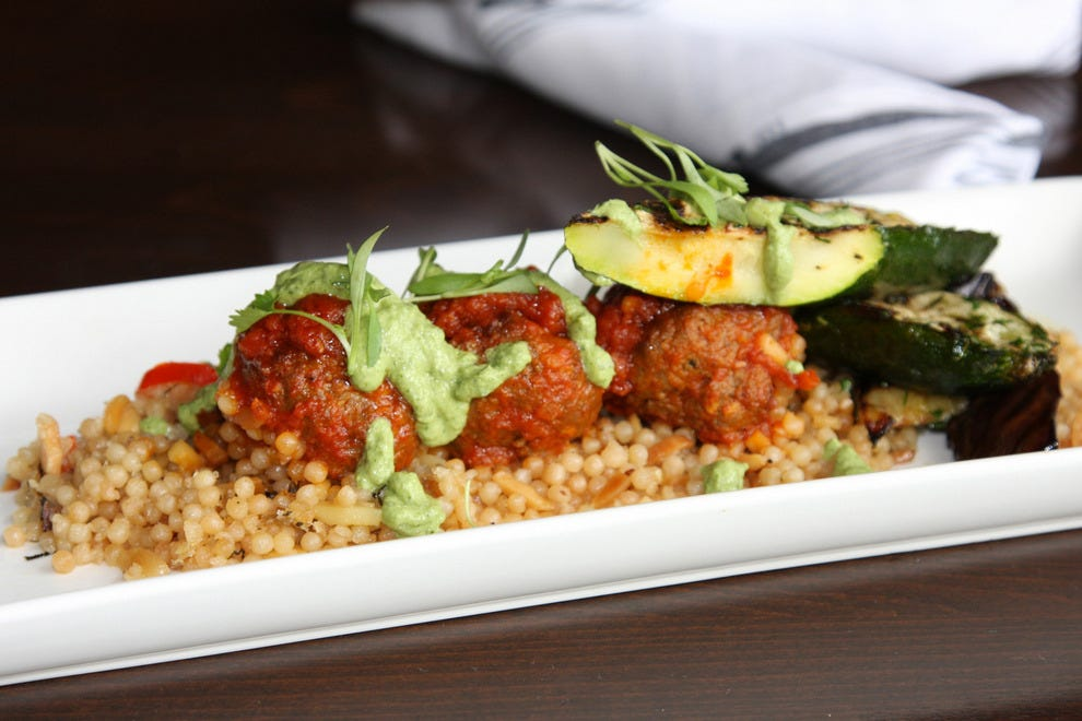 Lamb meatballs with grilled zucchini, eggplant, couscous, piquillos and tzatziki is one of the creative dishes on the lunch menu