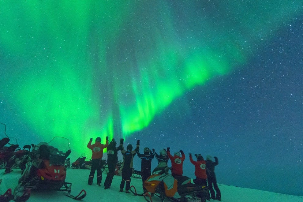 Snowmobilers cheer as Northern Lights halt their shore excursion from a Hurtigruten ship sailing Norway's northern coast