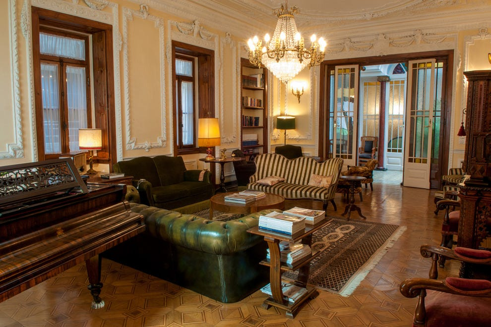 Vintage and reproduction furniture and antiques decorate the hotel's classically styled lounge at Palacete Chafariz D'El Rei