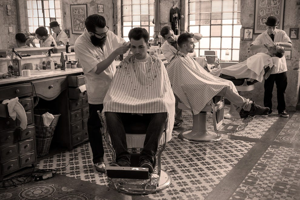 Customers seated in original Koken barber chairs attended to by staff at Figaro's Barbershop, in downtown Lisbon