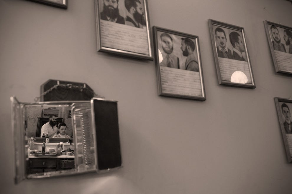 "A barber's mirror hung on a wall next to ""mugshots"" of Figaro staff reveals a detail of the interior"