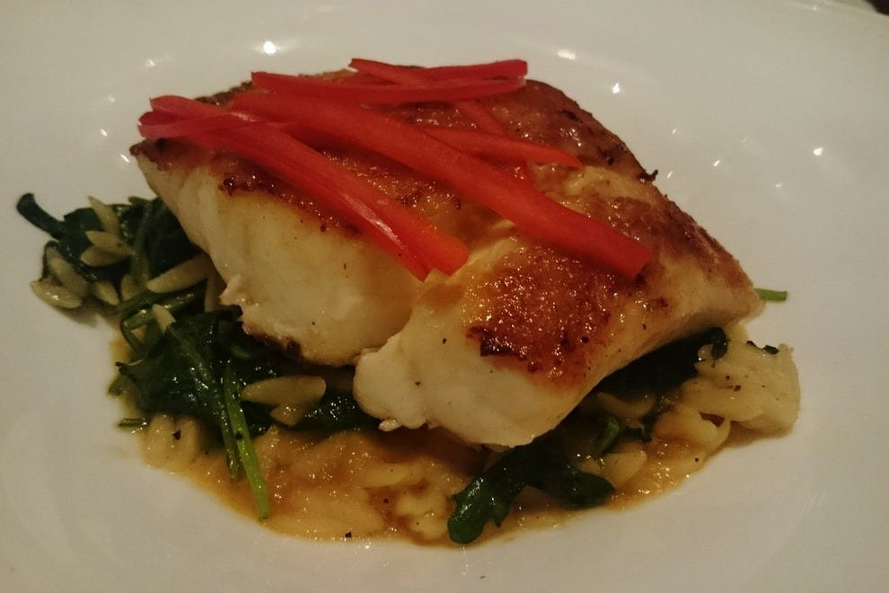 Beneath citrus-buttery sea bass lies spiced kale and lemongrass orzo