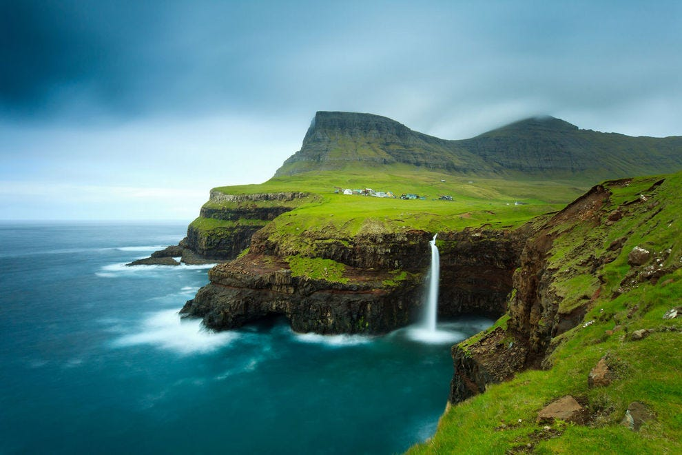 The picturesque village of Gasadalur can be found next to Heinanova mountain, with a waterfall cascading over a cliff into the Atlantic Ocean