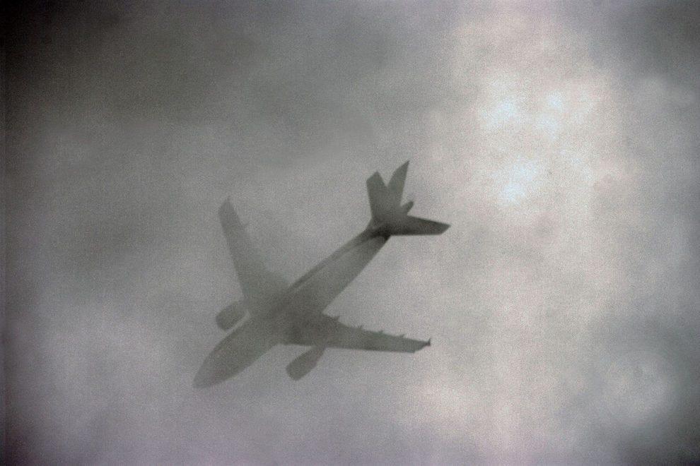 An airplane flies through spooky clouds