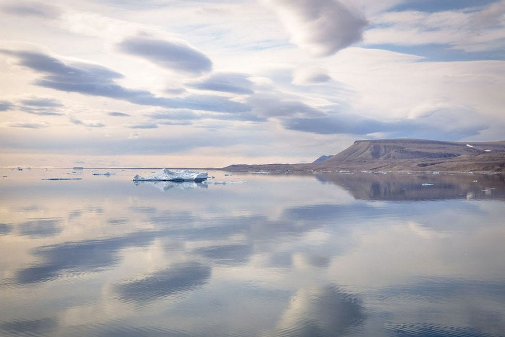 The still waters of Croker Bay create reflections of ice, land and sky
