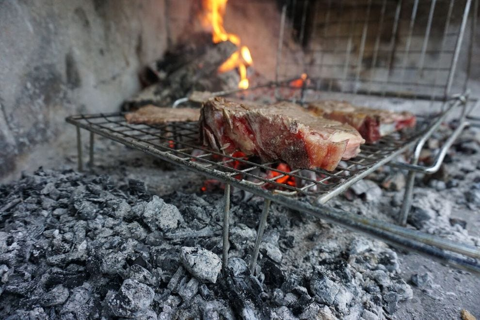 Steak cooking over embers