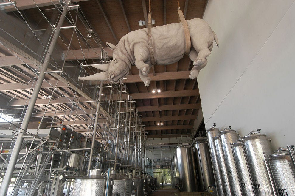 A rhinoceros by artist Stefano Bombardieri hangs over the fermentation tanks at Ca' del Bosco in Franciacorta, Italy