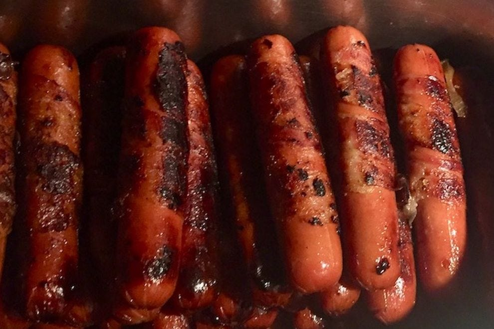 Bacon-wrapped hot dogs ready for topping at Los Ponchos