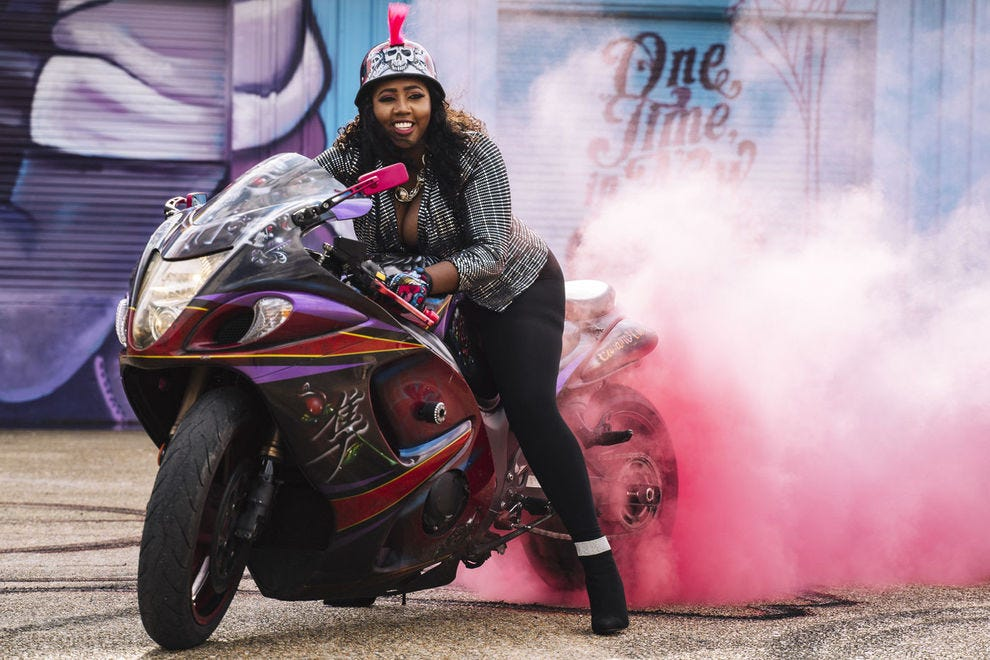 "One of the founding members of Caramel Curves, Shanika ""Tru"" McQuietor, burns their signature pink smoke"