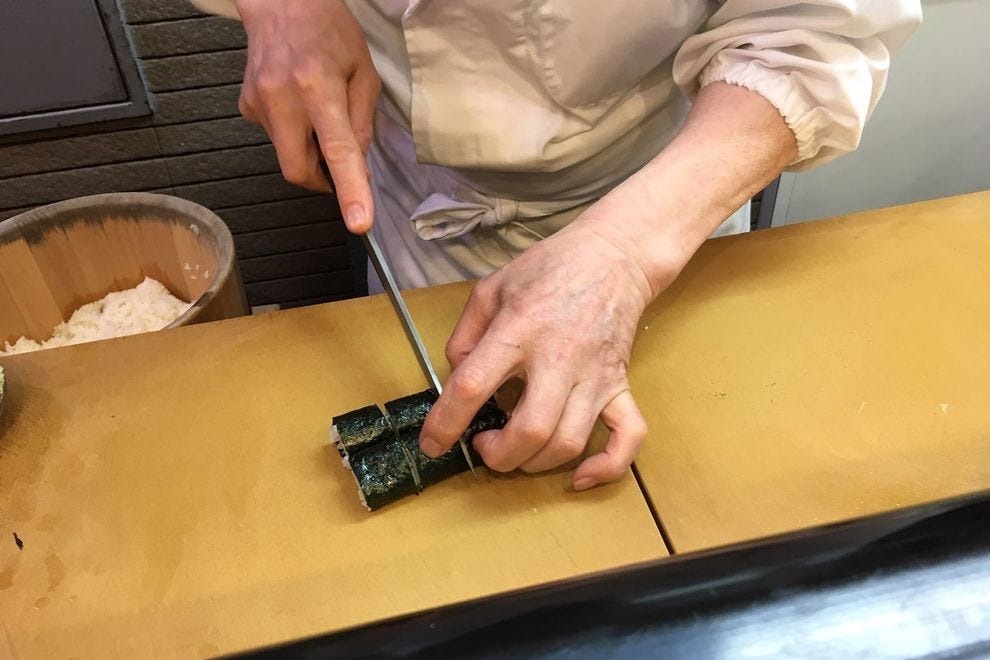 Sushi chefs use an array of specialized, ultra-sharp knives, in this case cutting the roll into bite-sized pieces