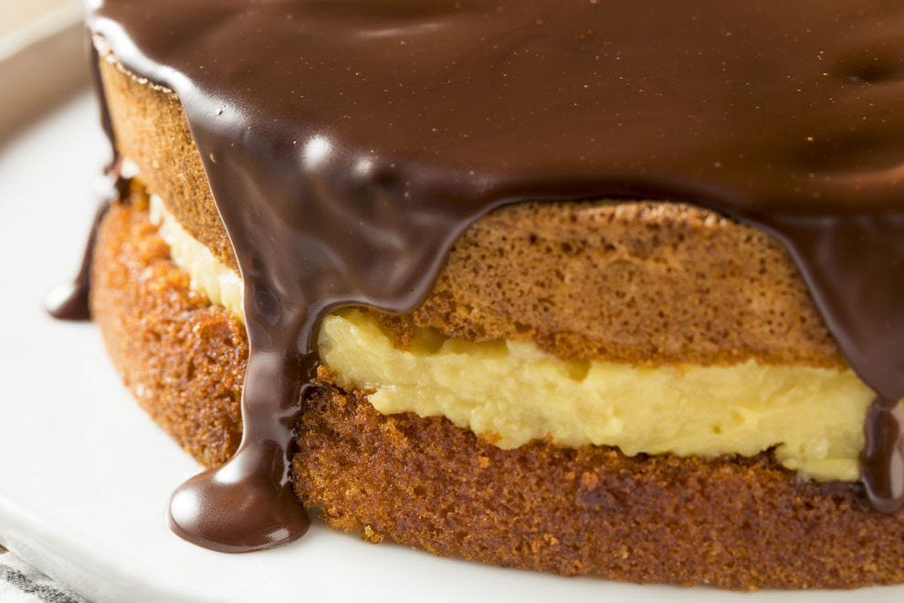Chocolate ganache cascades invitingly down the sides of a Boston cream pie