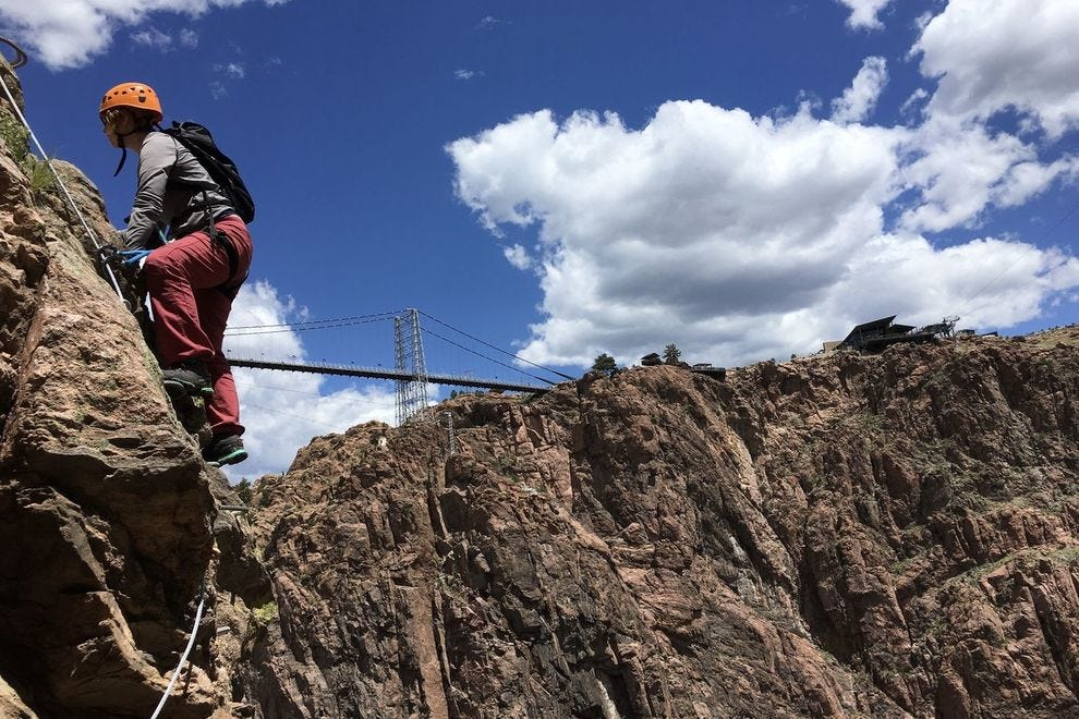 The author climbs Cañon City's new via ferrata, with the Royal Gorge bridge in the background