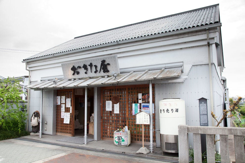 The white facade of Kitagawa Honke stands outs amidst the wooden-clad neighborhood.