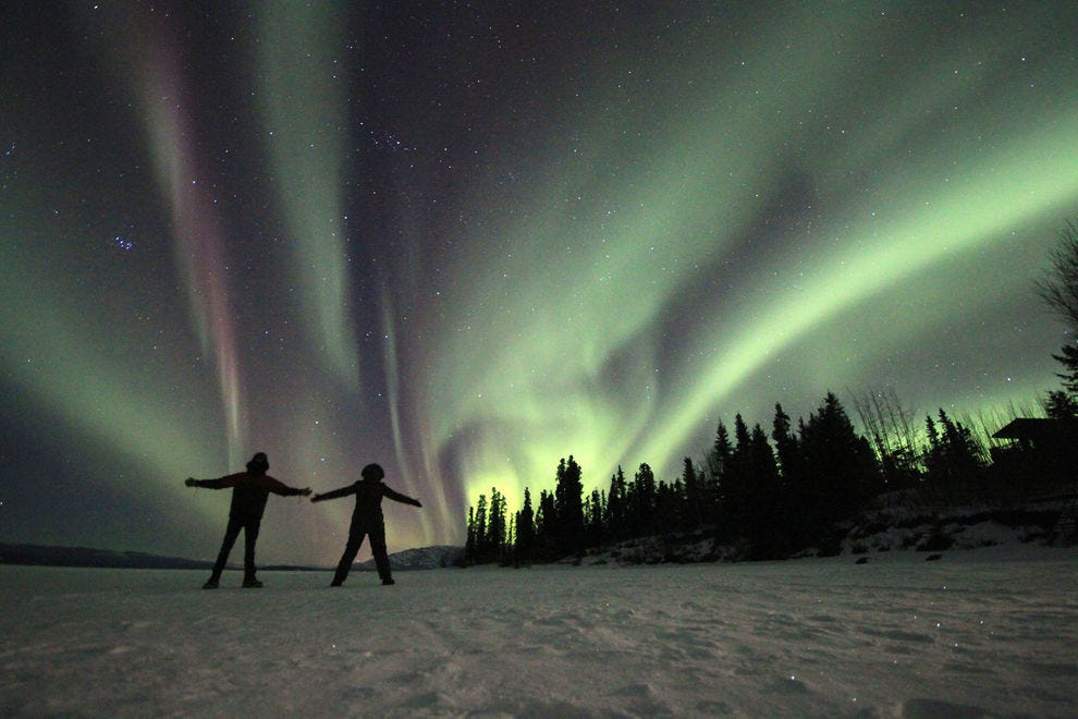 Two lucky revelers take in the northern lights while standing on a frozen lake