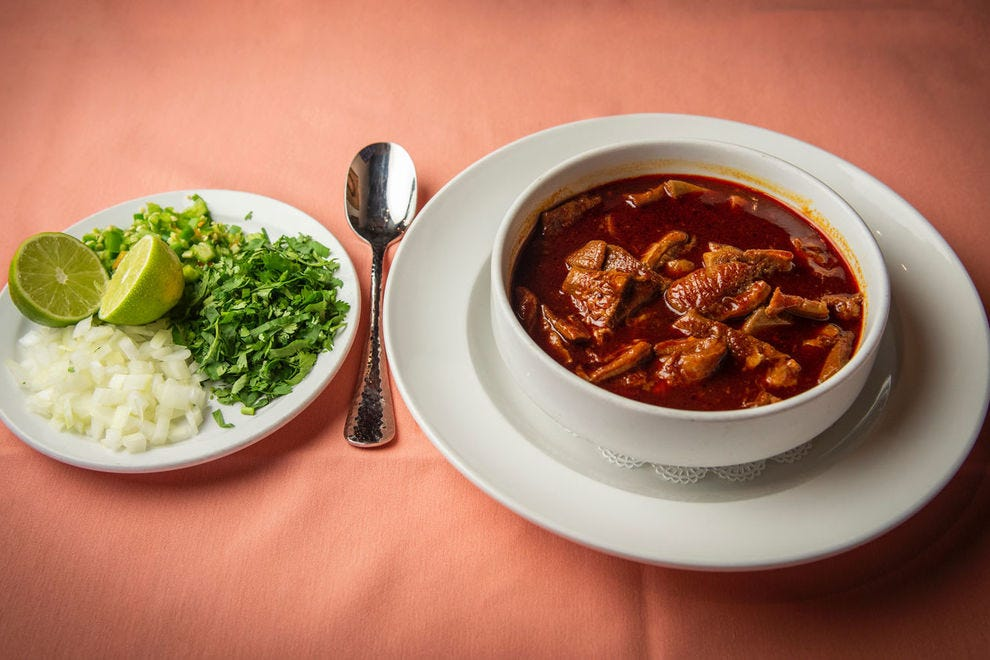 Picos Restaurant in Houston serves its menudo rojo with onions, cilantro, dried oregano, and lime wedges on the side to garnish