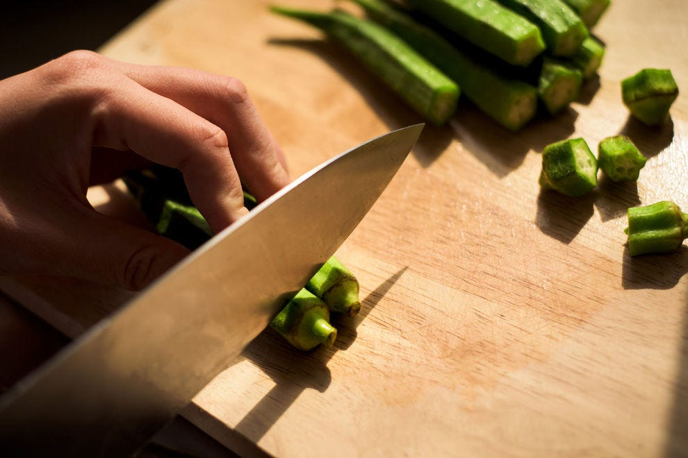 Slicing the stems off okra